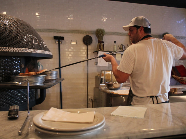 <p>Owner Stephen Menna cooks pizza at Tufino Pizzeria Napoletana, which opened at 36-08 Ditmars Blvd. on Tuesday, Dec. 18, 2012. The oven was built by hand in Naples, can reach temperatures as high as a thousand degrees and cooks pies in as little as two minutes.</p>