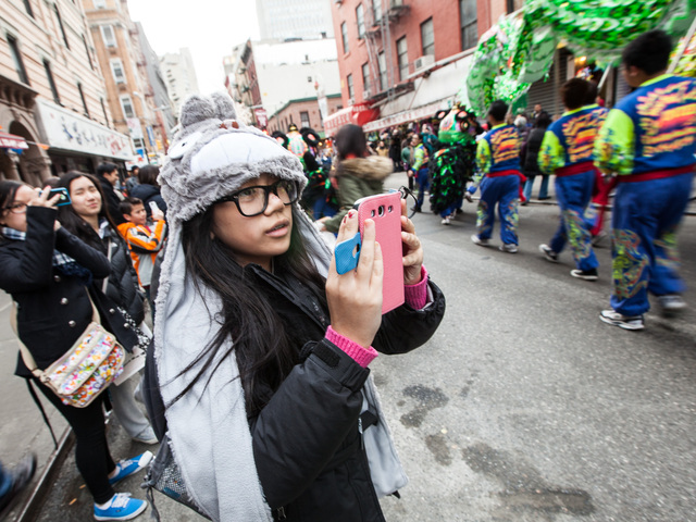 <p>A young girl takes pictures of the New York United Lion and Dragon Dance Troupe at the annual East Meets West Parade in Chinatown &amp; Little Italy on Dec. 22nd, 2012.</p>
