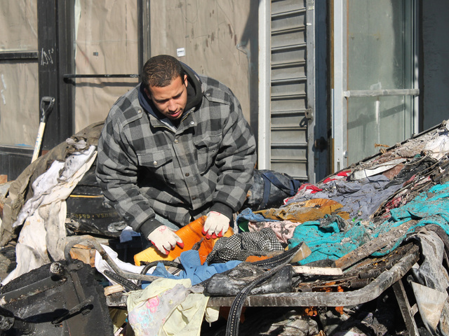 <p>A worker sorts through debris on Jan. 24, 2013, the day after a fire ravaged 2440 Amsterdam Ave.</p>