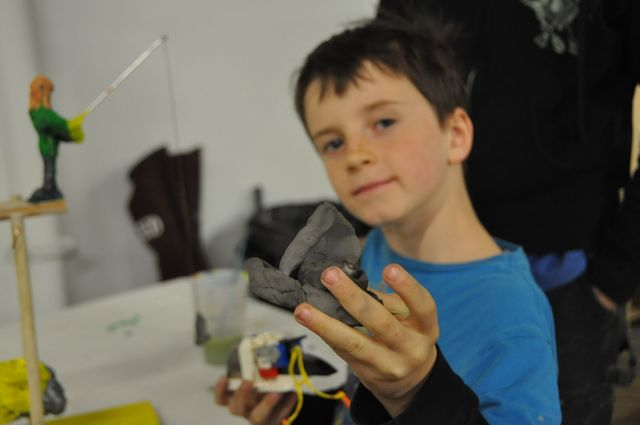 <p>Roman, 7, poses with a model he made out of clay at the Beam Center on Jan. 30, 2013.</p>