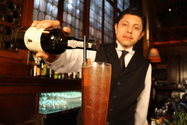 <p>Campbell Apartment bartender Raul Ortiz mixes up a Centennial Punch.</p>