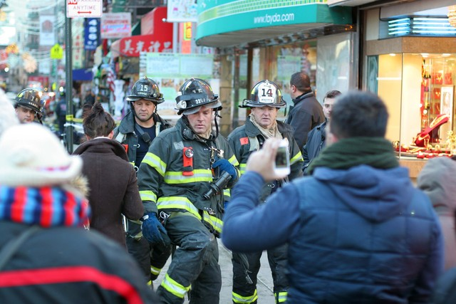 <p>Firefighters walk away from the scene of a large fire at 75 Mott St. on Jan. 27, 2013.</p>