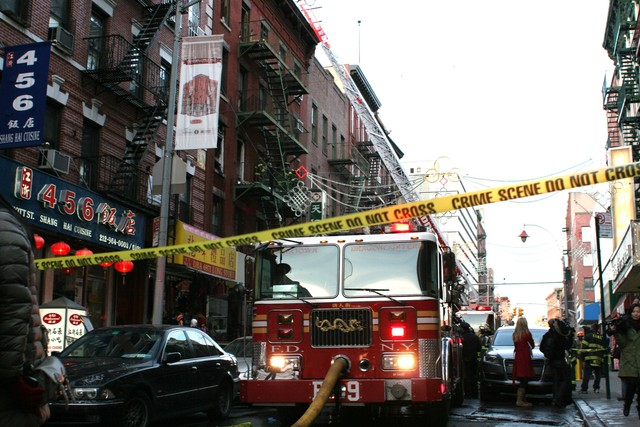 <p>Police tape at the scene of a large fire at 75 Mott St. on Jan. 27, 2013.&nbsp; Firefighters can be seen on the fire escape.</p>