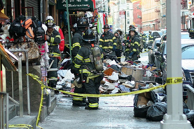 <p>Firefighters stand behind crime scene tape and next to a pile of debris at the scene of a large fire at 75 Mott St. on Jan. 27, 2013.</p>