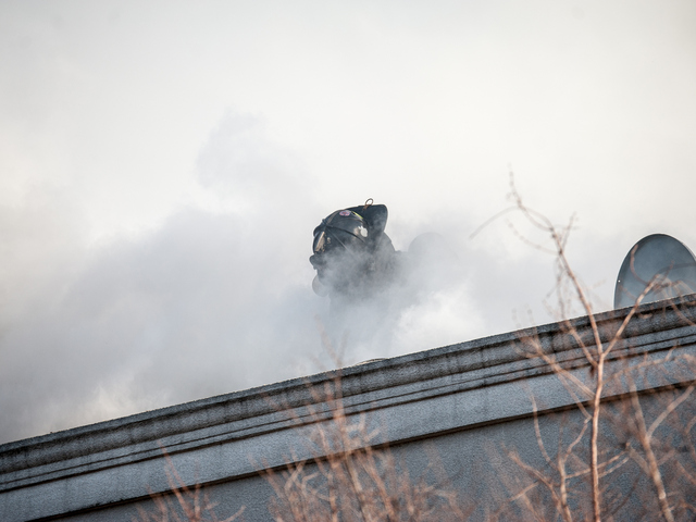 <p>A firefighter is swallowed up by thick smoke as he works on the roof of one of the buildings on Tuesday Jan. 22, 2013.</p>