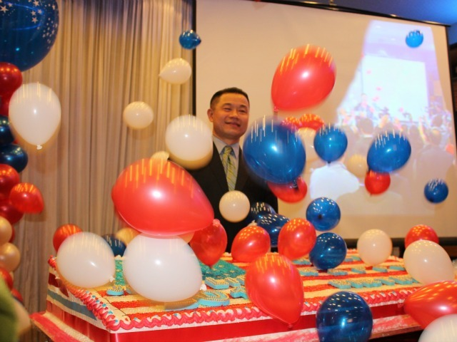 <p>Balloons cascade down after John Liu cuts his patriotic birthday cake at his January 2013 birthday party.</p>