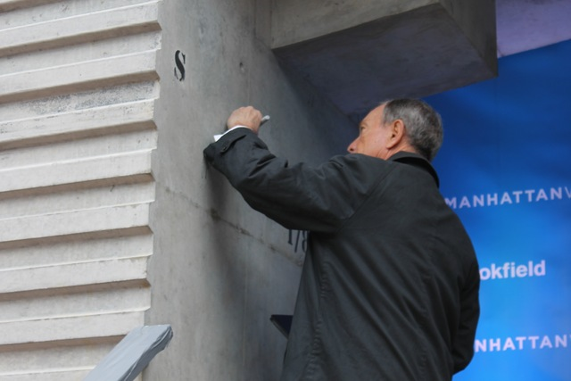 <p>Mayor Michael Bloomberg signs&nbsp;the concrete slab that will make up part of the platform over the rail yards.</p>