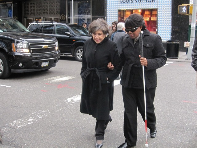 <p>Marie Gilles gets help crossing a street.</p>