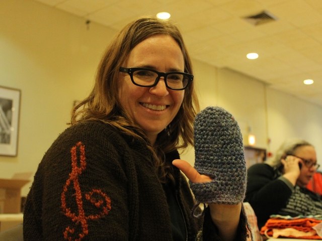 <p>Jessica Wolk-Stanley holds up a mitten she crocheted for the Ali Forney Center on Mitzvah Day.</p>