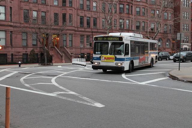 <p>A MTA bus turns at 120th Street and Mount Morris Park West. As an interim fix, the DOT has eliminated a turning lane at the intersection.</p>