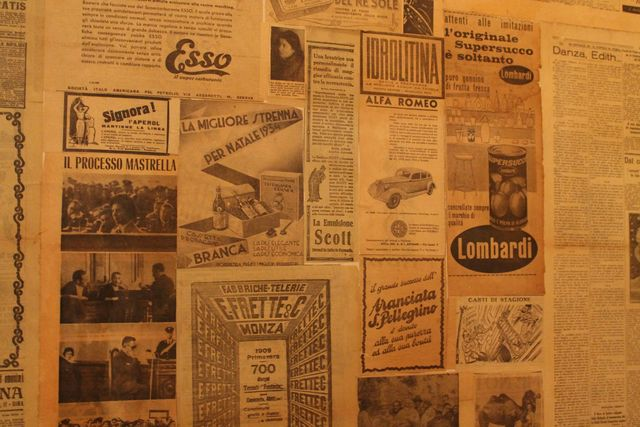 <p>The walls are lined with vintage newspapers from Italy in the 1920s.</p>