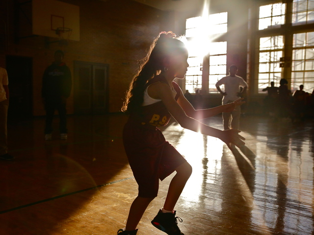 <p>A young girl dribbles the ball in preparation for a P.S. 67 basketball game.</p>