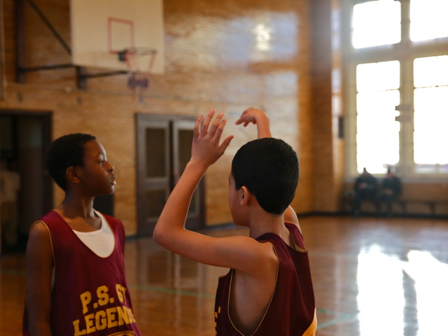 <p>Boys prep for a P.S. 67 basketball game.</p>