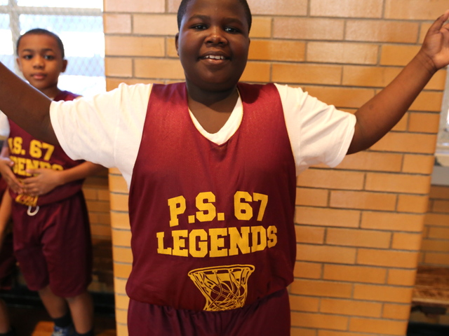<p>A young boy shows off his new jersey before a P.S. 67 basketball game.</p>