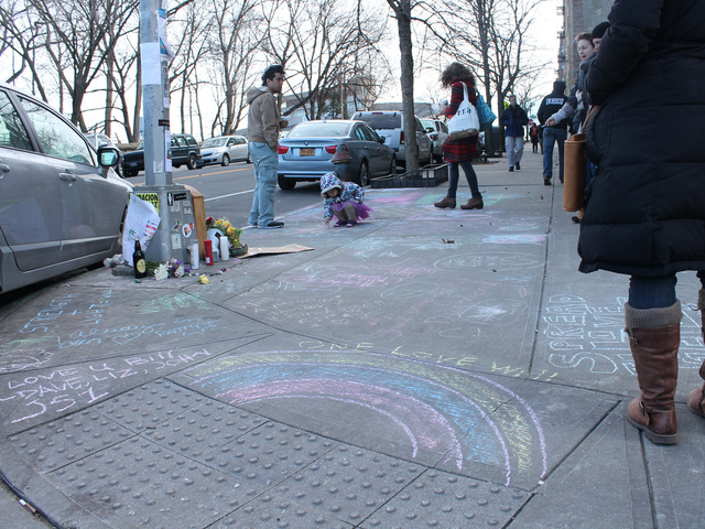 <p>Residents have left messages in chalk on the sidewalk surrounding the shrine.</p>