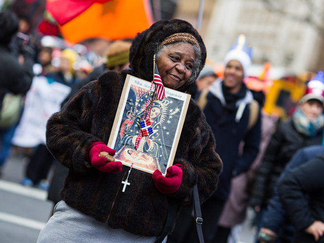 <p>A woman holds a holy icon and the American flag during the 36th Annual Three Kings Day Parade in East Harlem on Jan. 4, 2013.</p>