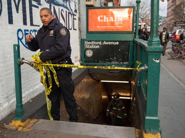 <p>A police officer secures the scene at the Bedford Avenue stop for the L Train, where a woman was struck on Monday Jan. 21, 2013.</p>