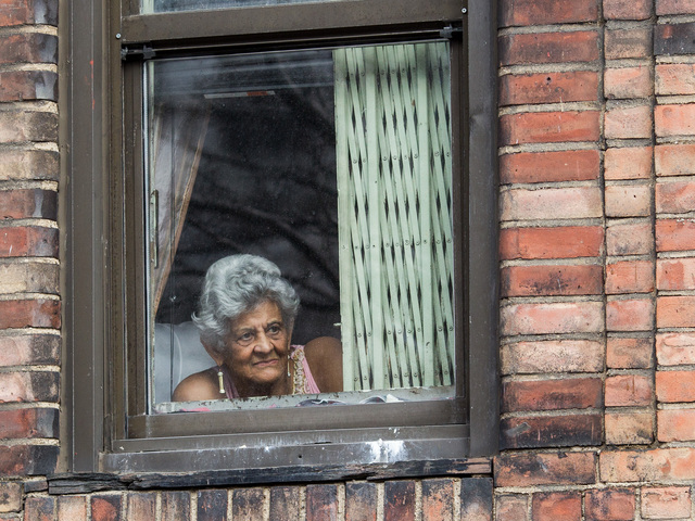 <p>A woman takes in the Annual Three Kings Day Parade from her apartment window in East Harlem on Jan. 4, 2013.</p>