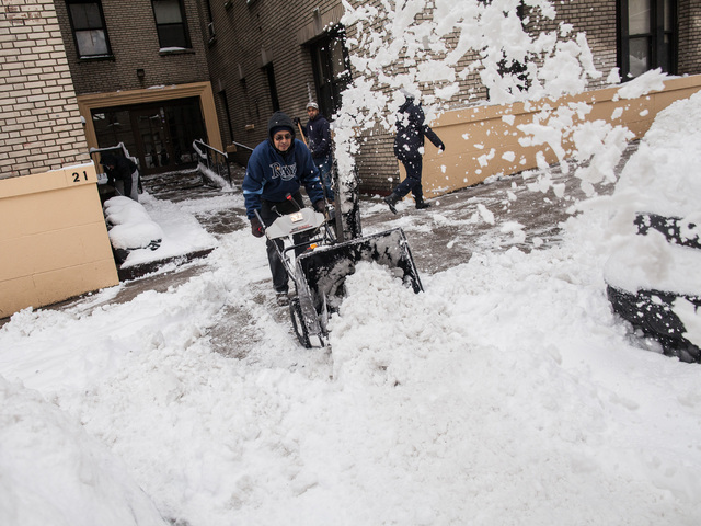 <p>Building workers in Washington Heights use a snow blower to clear a sidewalk of snow on Bennett Ave after a the city was hit with 11 inches of snow on Feb. 9, 2013.</p>