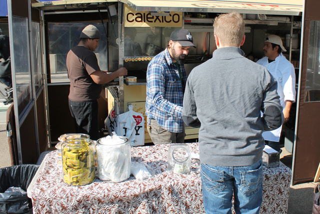 <p>Calexico line cook Anthony Suarez, second from left in black hat, seen here serving a customer in Worth Square Feb. 15, 2013, said he would welcome a market in the plaza. &quot;It&#39;s actually a lot of fun for us,&quot; Suarez said.</p>