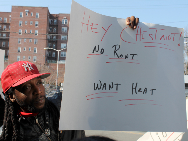 <p>A critic of landlord Chestnut Holdings holds up a sign at a rally on Feb. 15, 2013.</p>