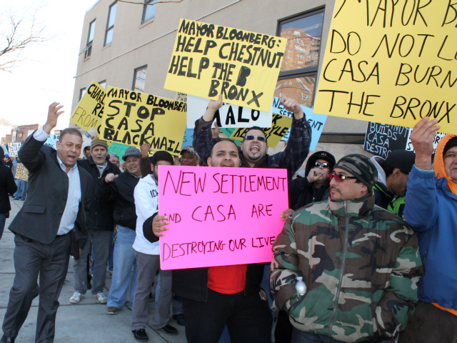 <p>Cesar Morales (left, in suit), a Chestnut Holdings field manager, encourages the landlord&#39;s supporters to cheer loudly, drowning out a nearby tenant protest. Some of the rally participants carried signs denouncing the nonprofit groups who have helped organize tenants.</p>