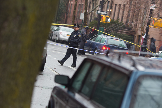 <p>An officer watches the intersection of Clinton Street, near Sackett Street, in Brooklyn after a woman was found with a head wound on Feb. 22, 2013.</p>