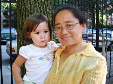 Dr. Lotus King Weiss, who is applying to open six bilingual Chinese schools, holds her daughter.