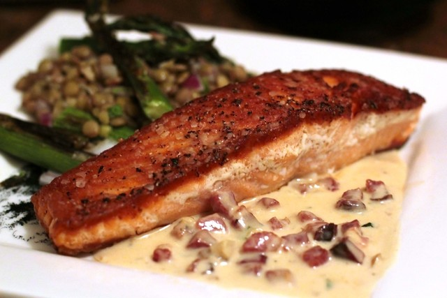<p>This delicious salmon dish pairs a cold lentil salad with a rich Dijon mustard sauce with bacon that plays on the traditional concept of smoked slamon.</p>