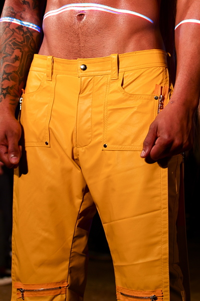 <p>Detail of yellow leather knee length pants with utility details</p>