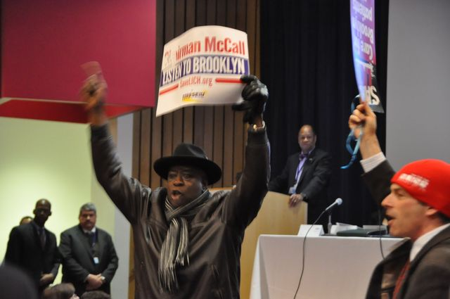 <p>A man raises his placard in protest during Dr. John Williams&#39; presentation on Feb. 7, 2013.</p>