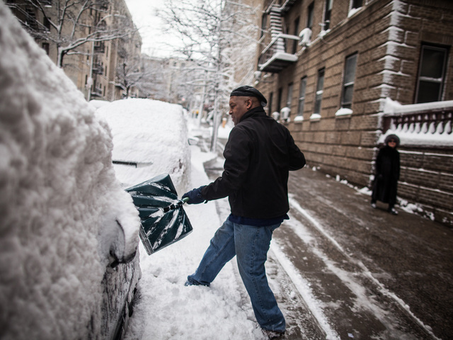 <p>Washington Heights resident Marcos Herbert, 51, digs out his Toyota Previa on Bennett Ave., on Feb. 9, 2013.</p>