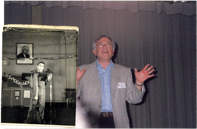 <p>Mel Zweidler stood on stage in J.H.S. 50 next to a photo of him on the same stage as a child.</p>