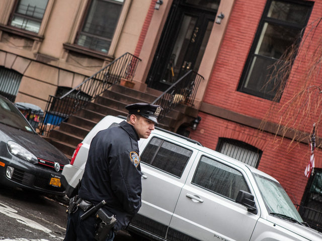 <p>An officer stands outside 388 Clinton St., where Elizabeth Borst, 55, was found Friday with a fatal head wound.</p>