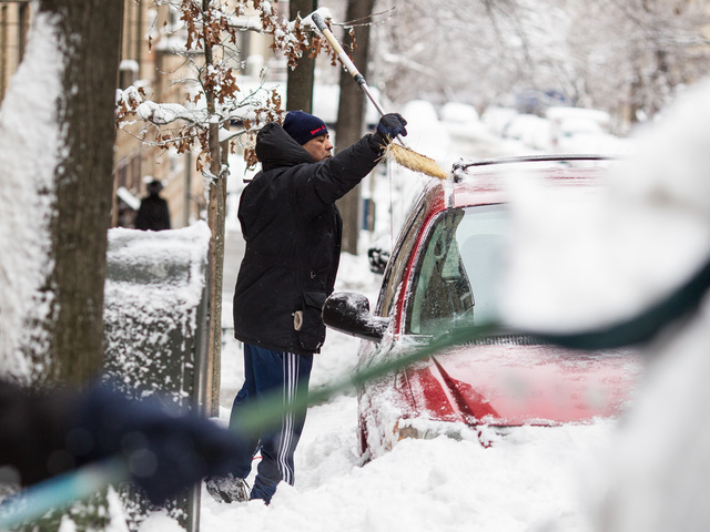 <p>Residents in Washington Heights clear snow from their vehicles after a snow storm hit New York City on Feb. 9, 2013.</p>
