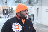 <p>Reuben &quot;Big Rube&quot; Harley wears an orange beanie with a scarf and jacket with orange accents.</p>