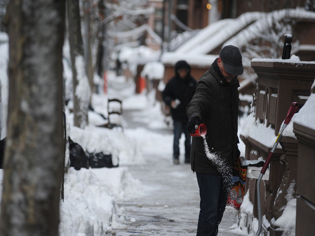 <p>A man tosses salt down on the sidewalk after the snowstorm on Feb. 9, 2013.</p>