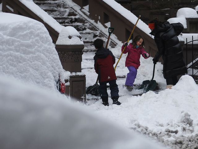 <p>A family uses teamwork to shovel a walkway on West 70th Street on the Upper West Side on Feb. 9, 2013.</p>