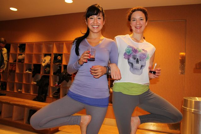 <p>Francesa Valarezo and Dana Slamp, a Pure Yoga teacher, take tree pose while sipping wine.&nbsp;</p>