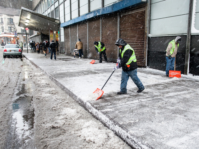 <p>Transit workers clear snow from the sidewalk outside the George Washington Bus Terminal in Washington Heights on Feb. 8, 2013.</p>