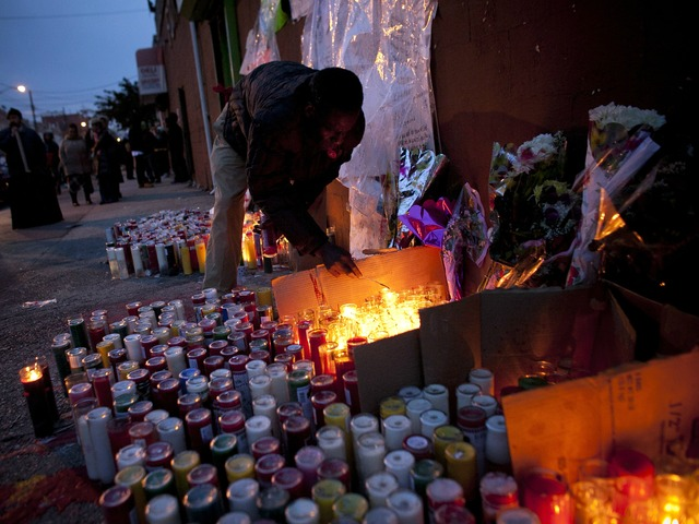 <p>A man lights candles at a memorial for Kimani Gray, March 13, 2013 in the East Flatbush neighborhood of the Brooklyn borough of New York City. 16-year-old Kimani Gray was shot and killed by police on March 9, provoking protests and unrest in the neighborhood.</p>