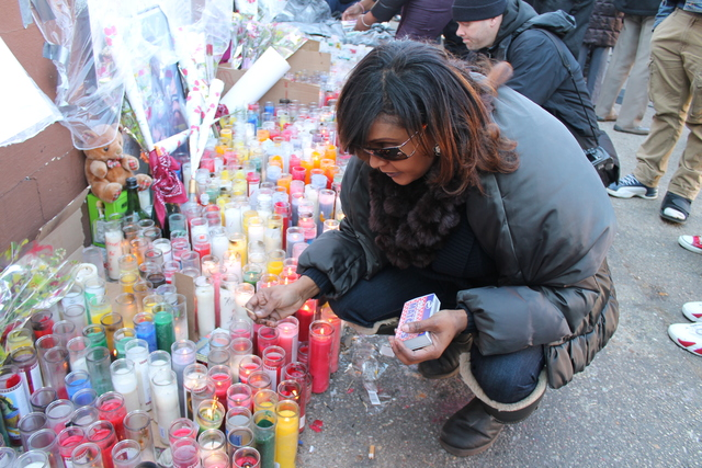 <p>Sandra Mitchelin, 42, a close friend of the Gray, family, lights a candle in honor of Kimani, who was shot dead by police Saturday.</p>