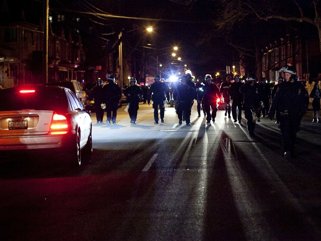 <p>Police patrol a protest against the shooting of Kimani Gray, March 13, 2013 in the East Flatbush neighborhood of the Brooklyn borough of New York City. 16-year-old Kimani Gray was shot and killed by police on March 9, provoking protests and unrest in the neighborhood.</p>