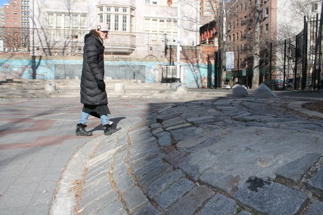 <p>Parent Association President Christine DiPasquale demonstrates the uneven cobblestones at the playground.&nbsp;</p>