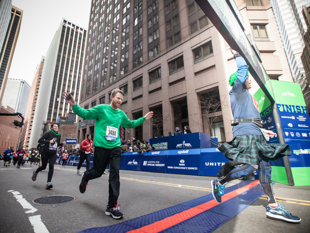<p>A runner crosses the finishing line of the annual NYC Half marathon at the South Street Seaport on Mar. 17, 2013.</p>