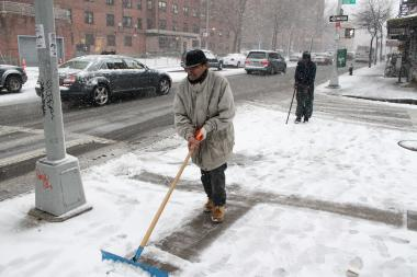 A business owner clears the sidewalk at Dekalb Avenue and Kent Street on March 8, 2013.