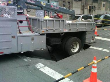 A Department of Environmental Protection truck got stuck in a sinkhole as workers responded to a Bronx water main break on April 20, 2013.