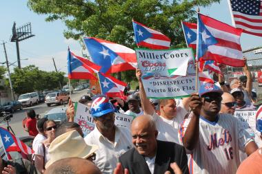 About 75 protesters, waving Puerto Rican flags, gathered outside of Manhattan Beer Distributors on E. 149th Street in the Bronx and said the announcement by MillerCoors that they would stop producing a Coors Light can that many felt contained a representation of the Puerto Rican flag, didn't go far enough.