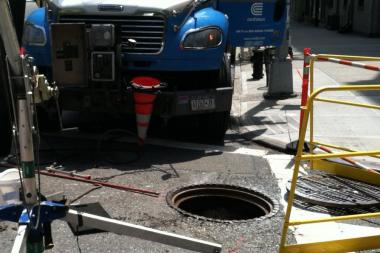 A manhole is uncovered after it exploded at 173rd Street in Washington Heights Friday, May 10, 2013 causing flames to erupt.