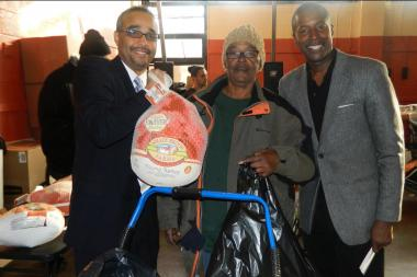 Jose Peralta, left, and Malcom Smith, right, give out a turkey to a constituent for the holidays.